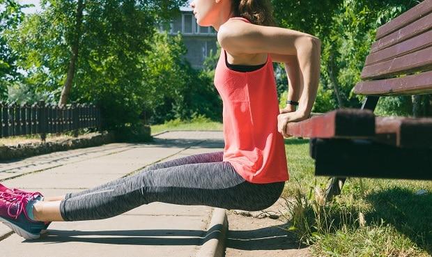 Девушка качает трицепс в парке