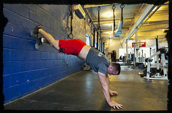 Мужчина выполняет упражнение ходьба по стене