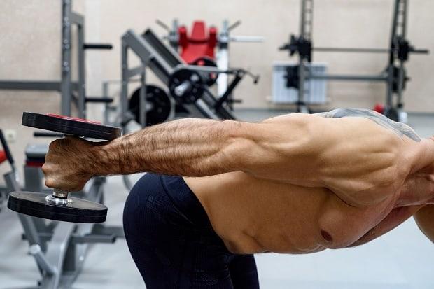 Мужчина делает упражнение на трицепс с гантелей