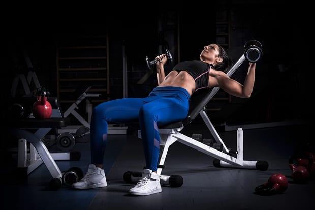 Тренировка груди в тренажерном зале девушкой