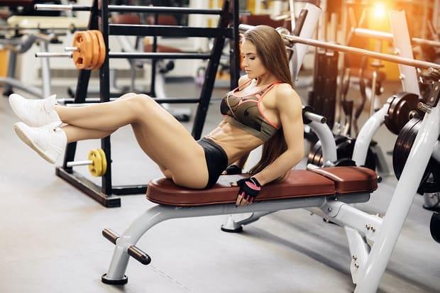 Девушка делает упражнение на пресс на скамье