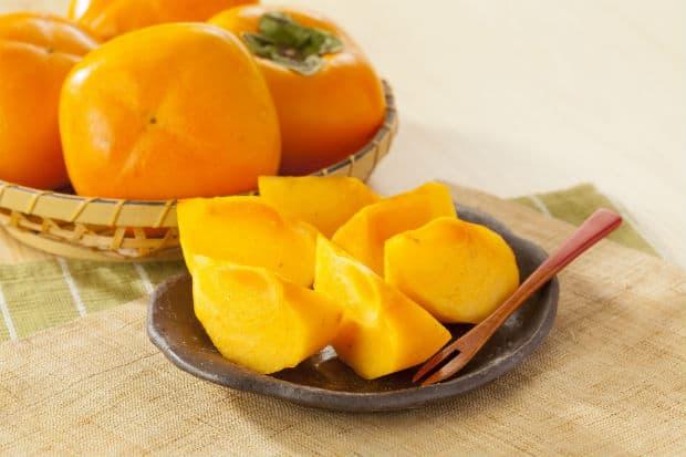 кусочки хурмы на тарелке и целые фрукты
