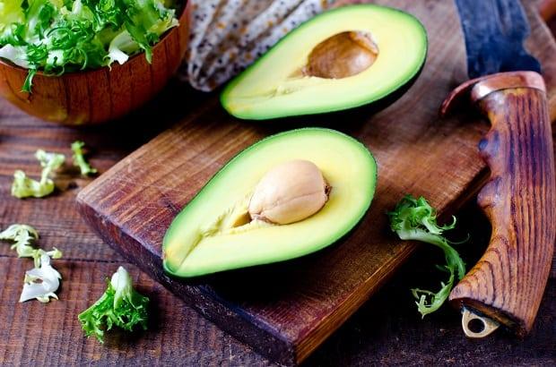 разрезанное пополам авокадо с косточкой на доске