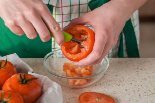 с помидора вырезается мякоть в прозрачную тарелку на столе
