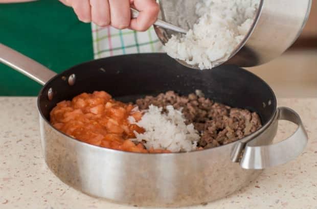 вареный рис перекладывается в сотейник с фаршем и нарезанными помидорами