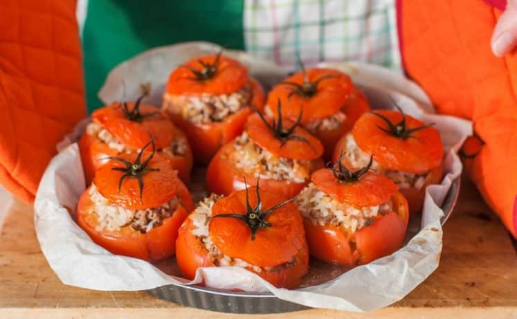 фаршированные помидоры с фаршем и рисом в форме для запекания, застеленной пергаментом