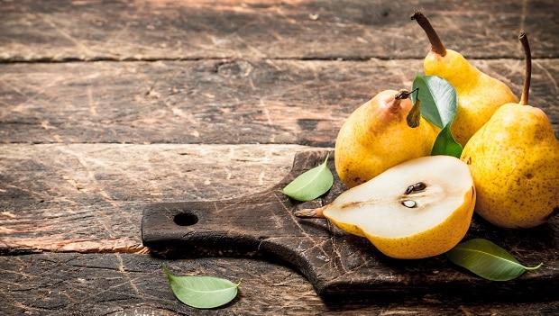 желтые груши с листвой на разделочной доске