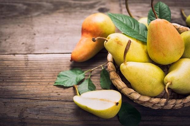 горка спелых груш в корзинке с листвой