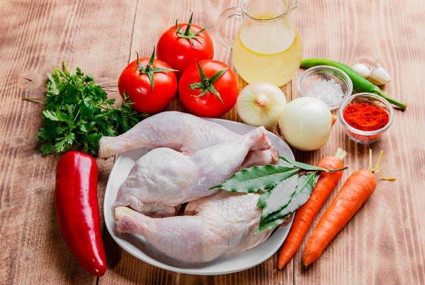 куриные четверти в тарелке, две морковки, три помидора, красный перец, зелень, лук, бульон в графине и специи