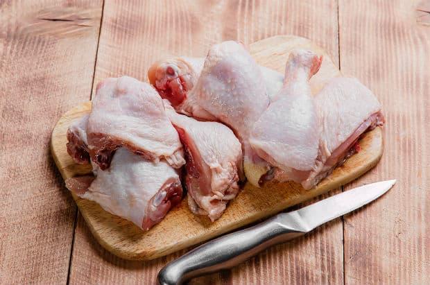 крупно нарезанные куриные четверти на разделочной доске на столе с ножом