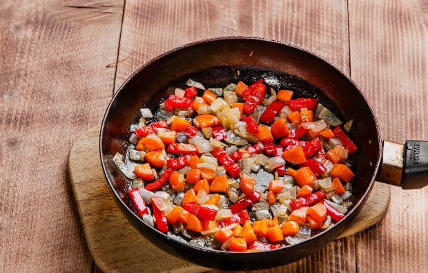 обжаренные кусочки лука, перца и моркови на сковороде на разделочной доске на столе