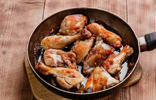 жареные кусочки курицы в сковороде на разделочной доске на столе