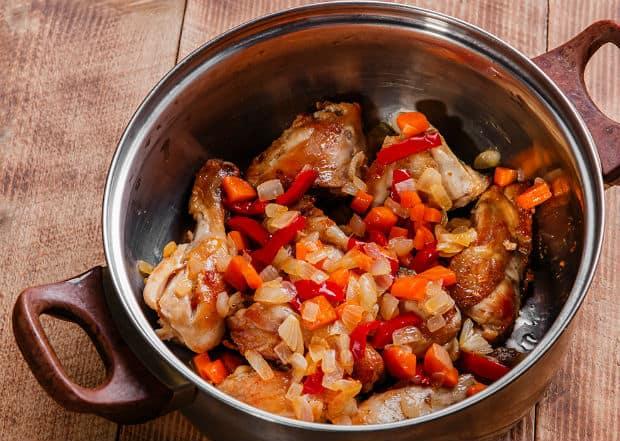 кусочки жареной курицы с морковкой, перцем и луком в кастрюле на столе