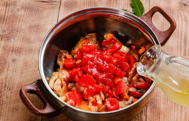 кусочки помидоров с курицей в кастрюле заливаются бульном