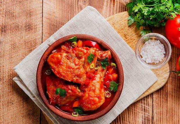 курица, тушенная с овощами, в глиняной посуде на доске, застеленной салфеткой, рядом пучок зелени и соль