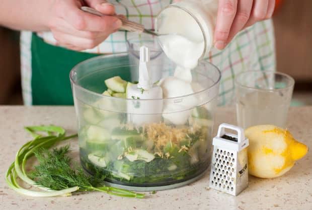 в блендер с зеленею и огурцом добавляется сметана, рядом маленькая терка и лимон без цедры