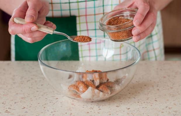 очищенные креветки в прозрачной миске, смесь специй в ложке и пиале
