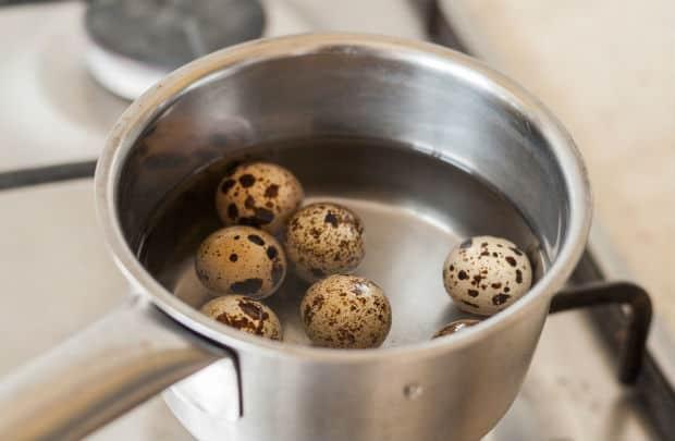 перепелиные яйца с водой в сотейнике на плите