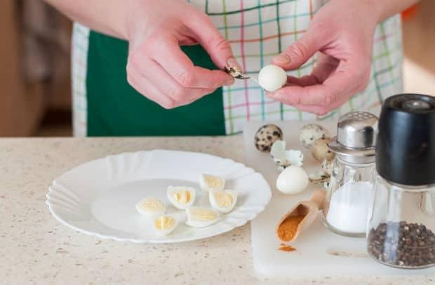 половинки вареных перепелиных яиц на белой тарелке, рядом яичная скорлупа, баночки с солью и перцем