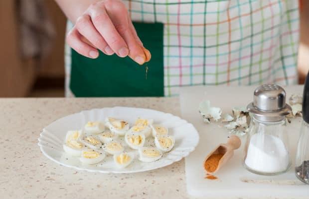 половинки вареных перепелиных яиц, посыпанные специями, на белой тарелке, рядом солонки