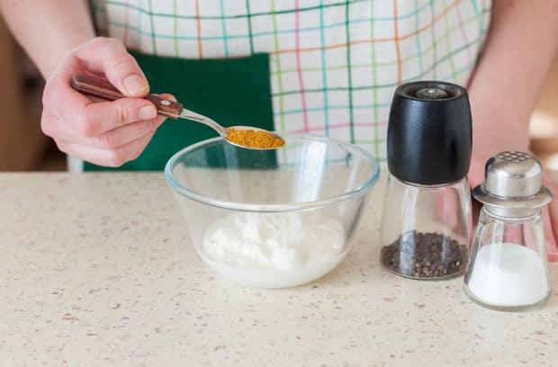 специи в ложке, сметана в пиале, баночки с солью и перцем на столе