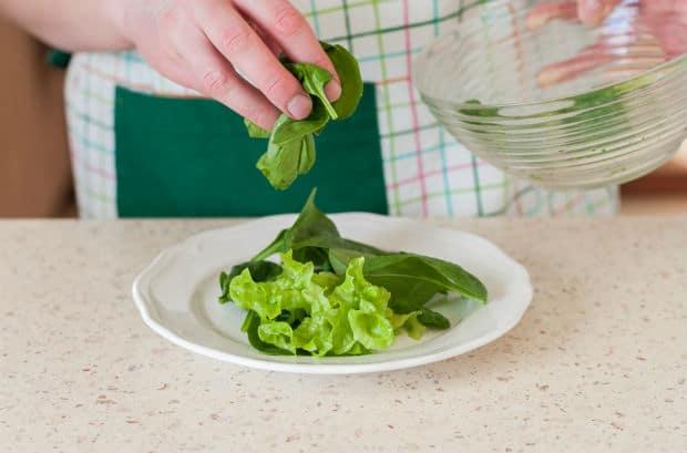 листья салата на белой тарелке на столе