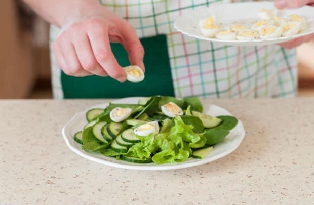 половинки вареных перепелиных яиц поверх листьев салата и огурцов на белой тарелке на столе