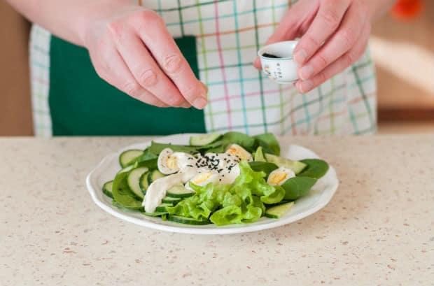 вареные перепелиные яйца с кусочками зелени и огурцов со сметаной и специями на белой тарелке