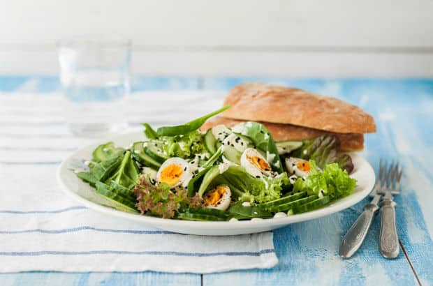 готовый салат с перепелиными яйцами, зеленью и огурцами на белой тарелке с кусочками хлеба, вилки на столе со скатертью
