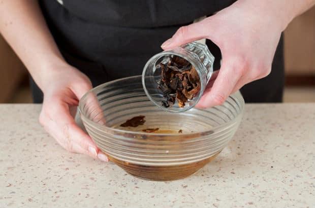 сушеные грибы высыпаются из стакана в тарелку с водой