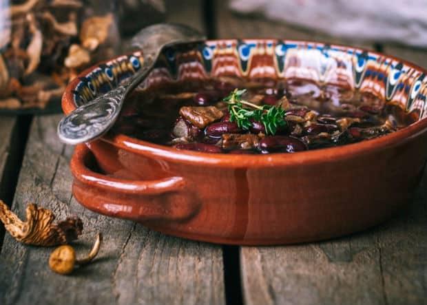 суп с фасолью и грбами в коричневой глиняной тарелке с ложкой