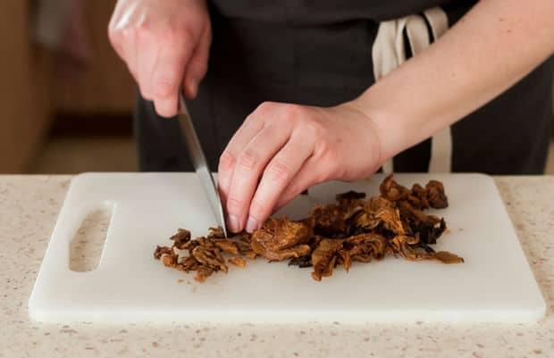 размоченные грибы нарезаются надом на разделочной доске
