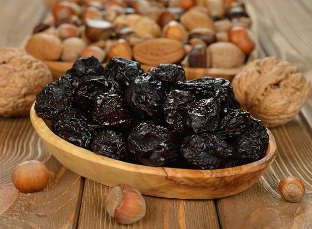 чернослив в деревянной тарелочке и орехи на столе