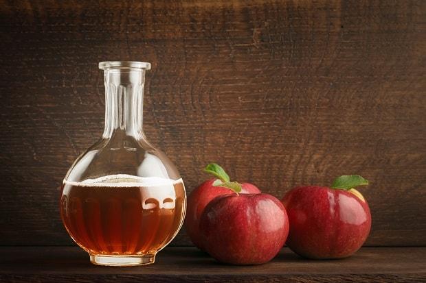 яблочный уксус и три красных яблока