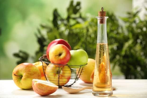 яблочный уксус в узком графине и свежие яблоки