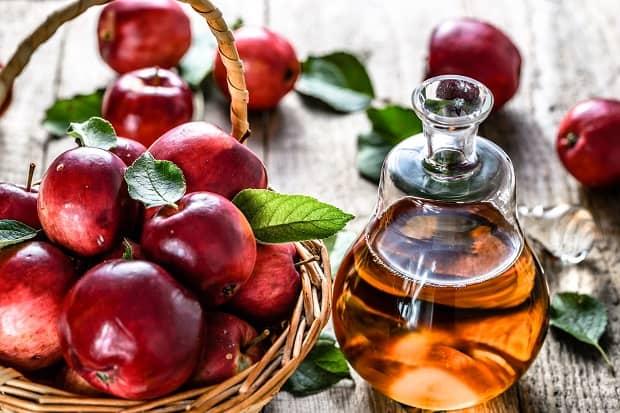 яблочный уксус в графине и яблоки в корзинке