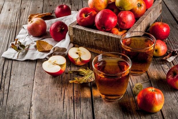 целые и разрезанные яблоки, яблочный сок в стакане