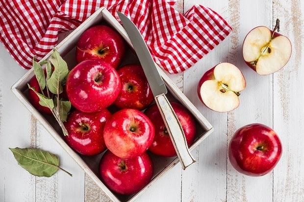 красные яблоки в коробке с ножом