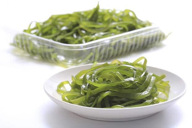 зеленая морская капуста на блюдце и в контейнере