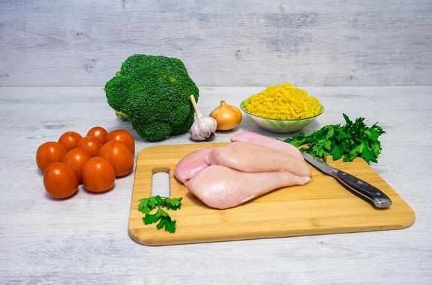 свежее куриное фил с ножом и зеленью на разделочной доске, рядом брокколи, помидоры, лук, чеснок и макароны в пиале