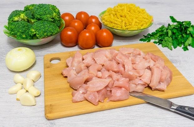 нарезанное куриное филе на разделочной доске, рядом помидоры, брокколи в тарелке, макароны в пиале, лук и чеснок