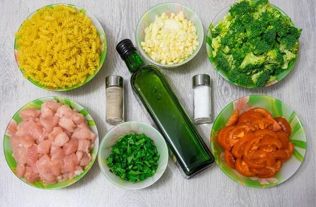 нарезанные помидоры, брокколи, зелень, куриное филе, лук и чеснок в тарелках, рядом макароны на тарелке, солонки и бутылка масла