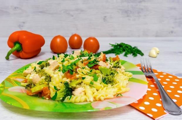 готовая паста с курицей, овощами и зеленью в тарелке, рядом филка на салфетке в горошек и помидоры на столе