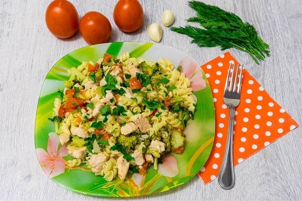 паста с курицей, овощами и зеленью на тарелке, рядом вилка на салфетке в горошек, помидоры, зубчики чеснока и зелень