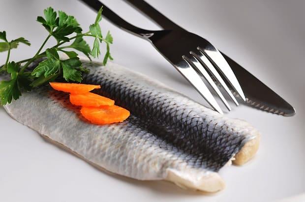 филе селедки с петрушкой, морковкой и вилка с ножом