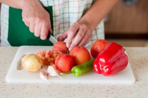 перец, помидоры без кожуры, лук, чеснок на разделочной доске