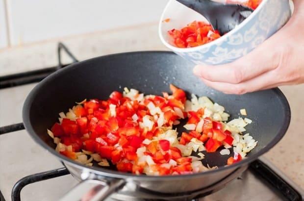 нарезанный красный перец с луком на сковороде на плите