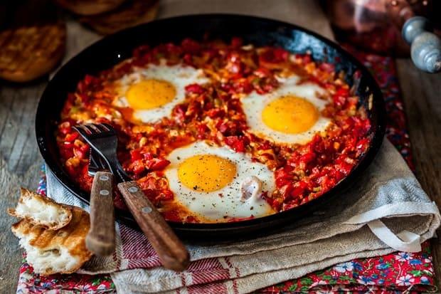 шакшука из трех яиц с овощами на сковороде с вилкой и ножом на столе, застеленном скатертью