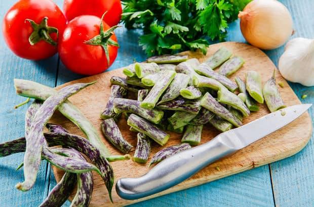 нарезанная стручковая фасоль на деревянной доске, рядом нож и свежие овощи