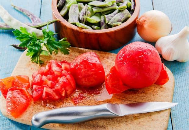 помидор очищенный от мякоти на деревянной доске, рядом нарезанная мякоть томата и нож
